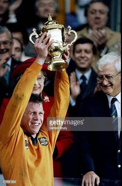 Australian Captain Nick FarrJones lifts the trophy after their victory in the World Cup final against England at Twickenham in London Australia won...