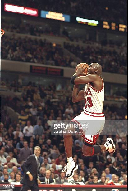 Guard Michael Jordan of the Chicago Bulls takes to the air in his famous moves to slam dunk against the Charlotte Hornets at the United Center in...