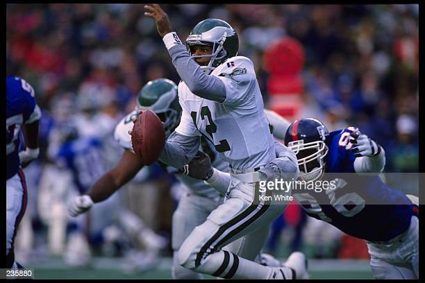 Quarterback Randall Cunningham of the Philadelphia Eagles scrambles out of the pocket and tries to avoid a diving Jamal Duff of the New York Giants...