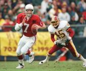 Boomer Esiason of the Arizona Cardinals runs from Washington Redskins defenders during the Cardinals 3734 overtime win at RFK Stadium in Washington DC
