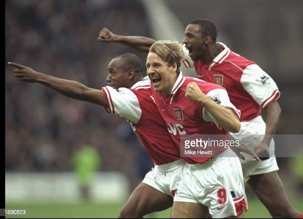 Ian Wright of Arsenal leads the celebrations with a little help from teammates Paul Merson and Patrick Vieira during the FA Carling Premier league...