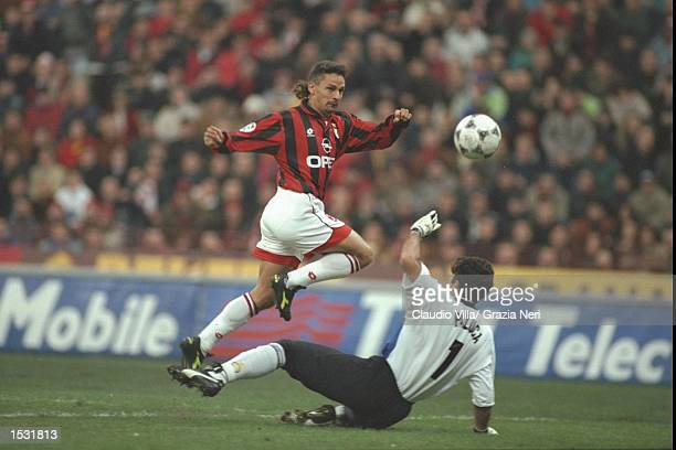 Roberto Baggio of Milan chips the ball over Gianluca Pagluica of Inter to score during the Serie A match between AC Milan and Inter Milan at the San...