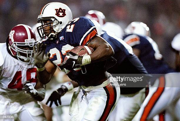 Fullback Fred Beasley of the Auburn Tigers tries to carry the ball past Trevis Smith of the Alabama Crimson Tide during a game at the JordanHare...
