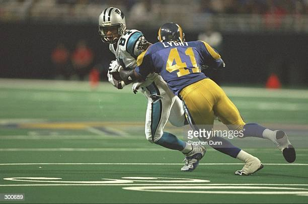 Rae Carruth of the Carolina Panthers in action as Todd Lyght of the St Louis Rams tries to make the tackle the Trans World Dome in St Louis Missouri...