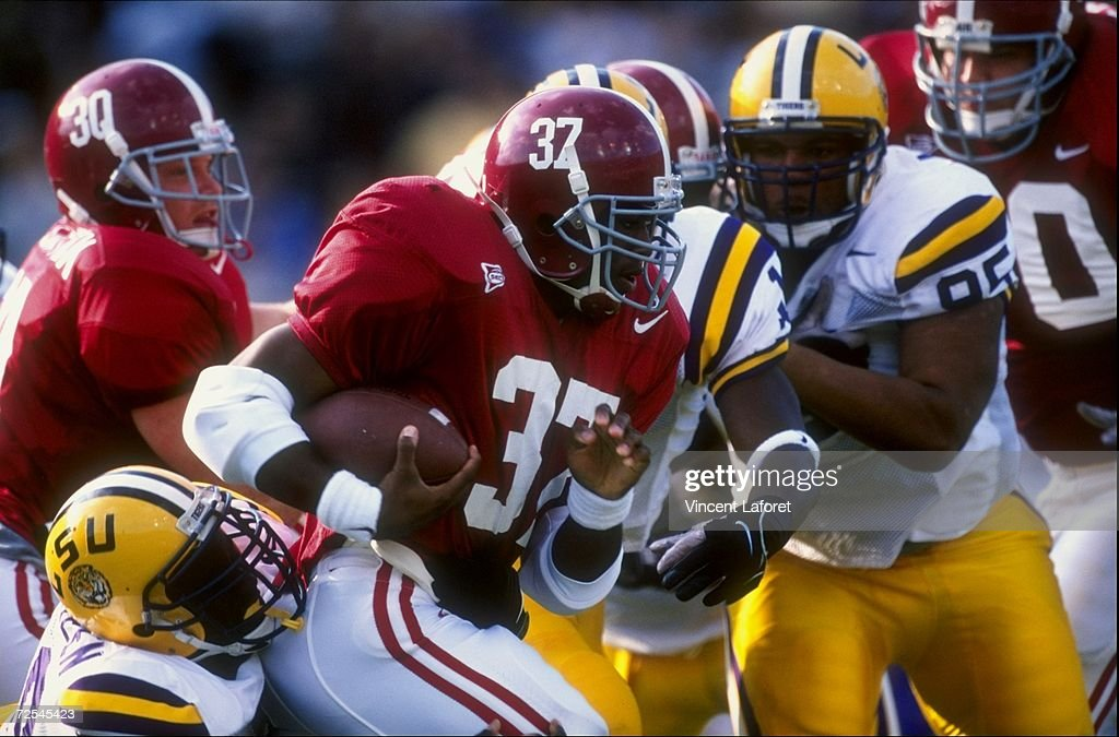 Running back Shaun Alexander of the Alabama Crimson Tide runs with the ball during a game against the Louisiana State Tigers at the Tiger Stadium in...