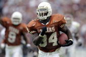 Tailback Ricky Williams of the Texas Longhorns breaks the NCAA career yards record while running with the ball during a game against the Texas AM...