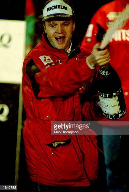 Tommi Makinen of the Mitsubishi Lancer EVO celebrates winning the Network Q Rally of Great Britain and crowned World Ralley champions Great Britain...