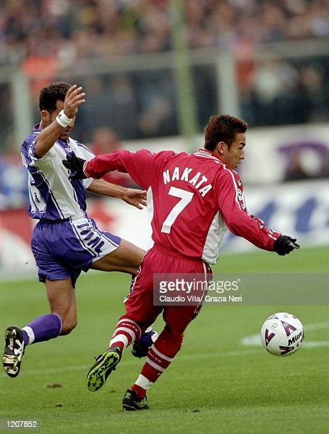 Hidetoshi Nakata of Perugia is challenged by Angelo Di Livio of Fiorentina during the Serie A match at the Artemio Franchi Stadium in Florence Italy...