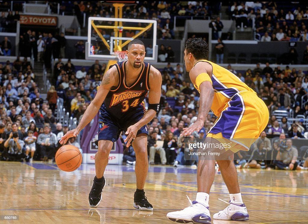 Chris Mills of the Golden State Warriors dribbles the ball as he is guarded by Rick Fox of the Los Angeles Lakers at the STAPLES Center in Los...