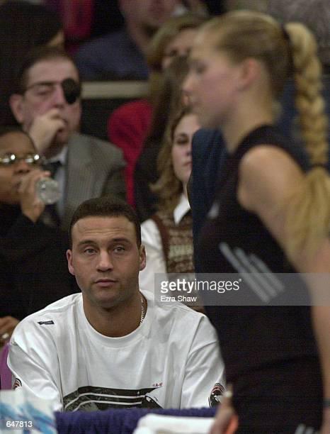 Derek Jeter of the New York Yankees watches Anna Kournikova of Russia during a change over in Kournikova's match against Conchita Martinez of Spain...