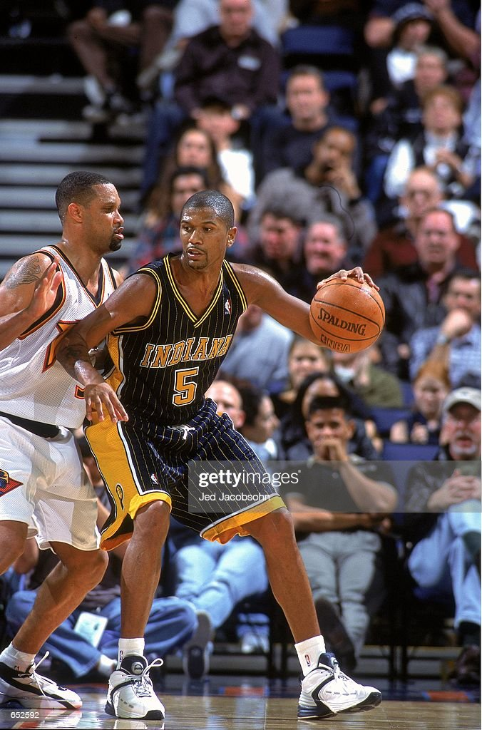 Jalen Rose of the Indiana Pacers dribbles the ball as he is guarded by Chris Mills of the Golden State Warriors at the Arena in Oakland California...