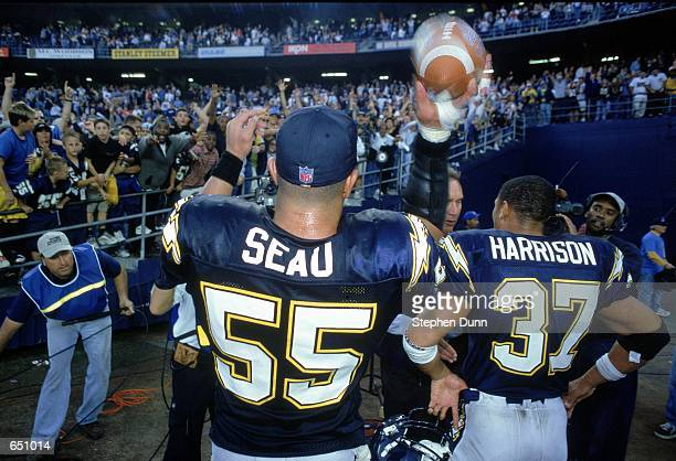 Junior Seau of the San Diego Chargers tosses a souvenir ball to fans with teammate Rodney Harrison after the game against the Kansas City Chiefs at...