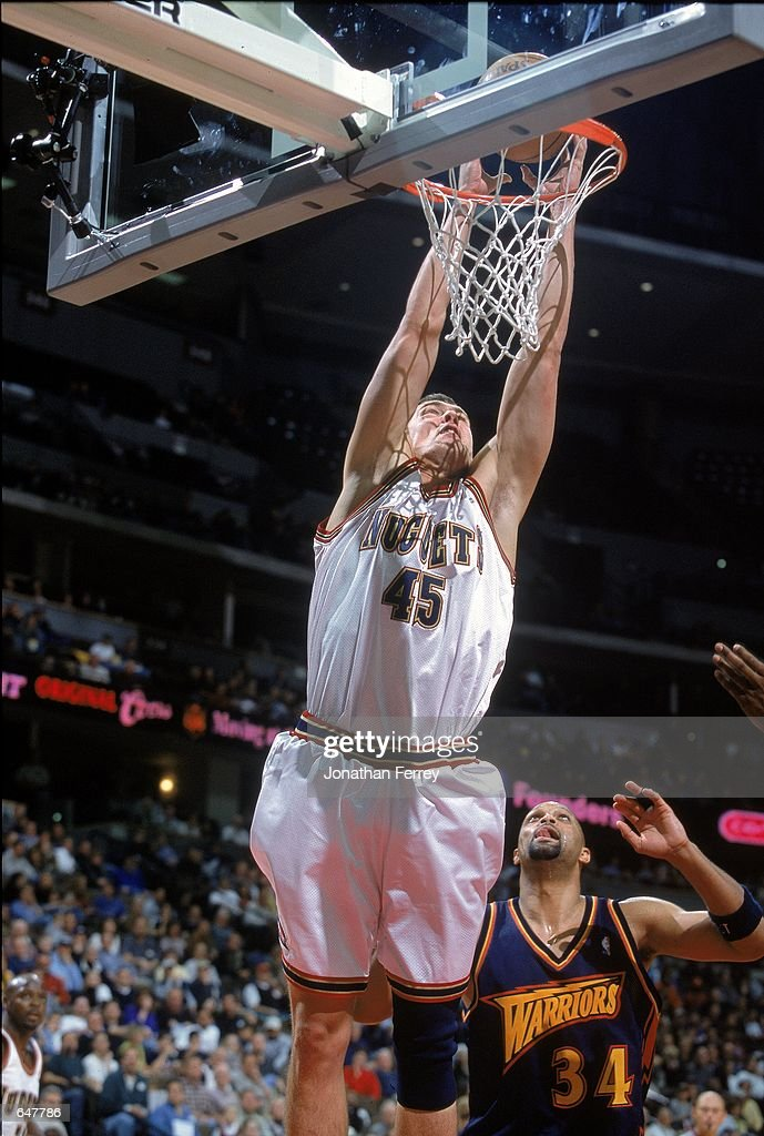 Raef La Frentz of the Denver Nuggets makes a slam dunk as Chris Mills of the Golden State Warriors watches at the Pepsi Center in Denver Colorado The...