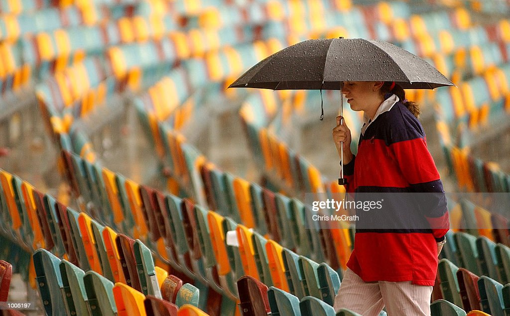 A cricket fan heads for cover after a thunderstorm stopped play during day four of the first cricket test between Australia and New Zealand held at the Gabba, Brisbane, Australia, DIGITAL IMAGE Mandatory Credit: Chris McGrath/ALLSPORT