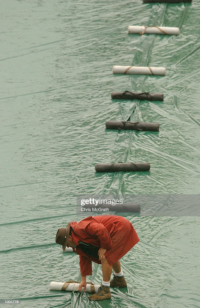 A Gabba grounds crew member weighs down the covers after rain stopped play in the first session during day two of the first cricket test between Australia and New Zealand held at the Gabba, Brisbane, Australia, DIGITAL IMAGE Mandatory Credit: Chris McGrath/ALLSPORT
