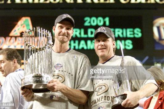 CoMVP winners Randy Johnson and Curt Schilling of the Arizona Diamondbacks hold the trophys after winning the World Series over the New York Yankees...