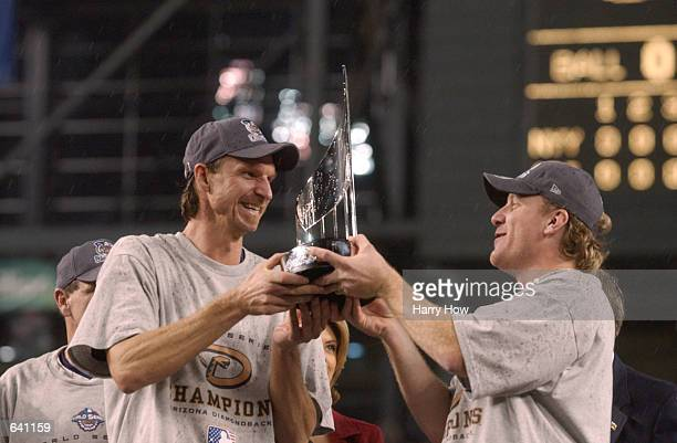 CoMVP winners Randy Johnson and Curt Schilling of the Arizona Diamondbacks hold the trophys after game seven of the Major League Baseball World...