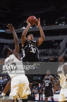 David West of the Xavier Musketeers takes a shot as he is blocked by Najeeb Echols of the Missouri Tigers during the game at the Conseco Fieldhouse...