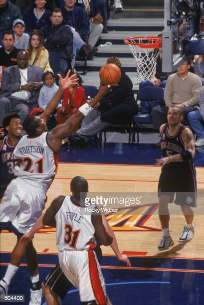 Forward Danny Fortson of the Golden State Warriors shoots past forward Jason Collins of the New Jersey Nets during the NBA game at the Arena in...