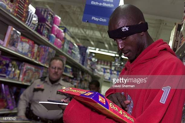 Kevin Garnett of the Minnesota Timberwolves tests an Etch A Sketch game while shopping for holiday gifts to be given to disadvantaged youth in...