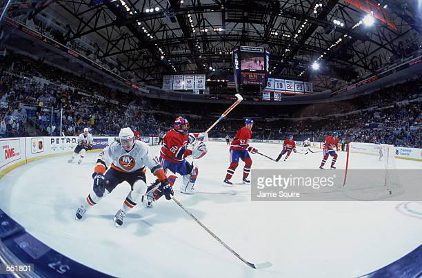Left wing Oleg Kvasha of the New York Islanders and goaltender Jose Theodore of the Montreal Canadiens skate on the ice during the NHL game at the...
