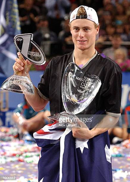 Lleyton Hewitt of Australia celebrates his victory over Sabastien Grosjean of France with the Championship trophy and the ATP number one trophy...