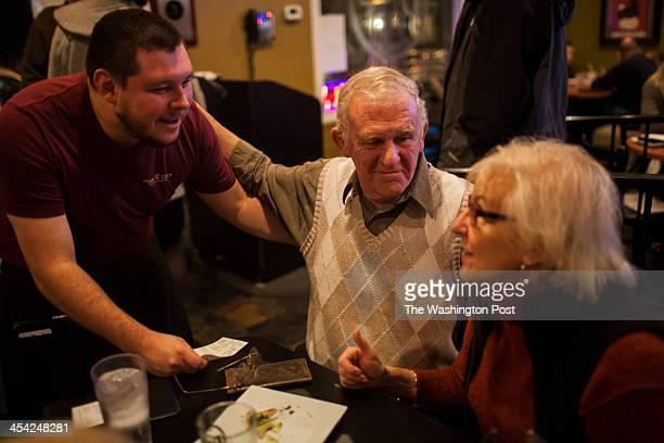 ALEXANDRIA VA Nov 26 Del Ray Pizzeria server Will Cowan left chats with Bruce Miller center and Kitty Porterfield right both of Alexandria Virginia...