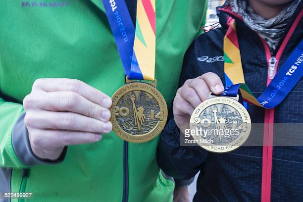 Nov 3 2014 Runners in the New York City Marathon show off their medals after finishing the race The Manhattan Borough of New York New York USA
