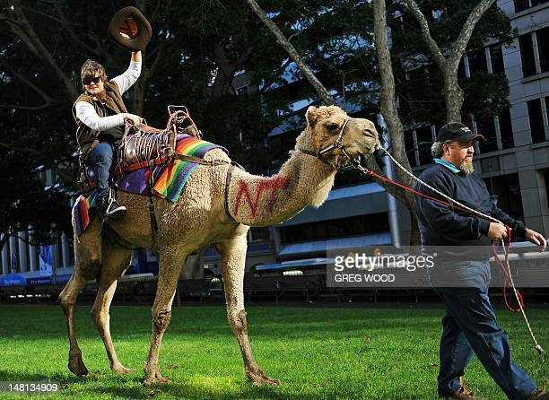 Nova Nights radio announcer Dean 'Deano' Thomas rides a camel affectionately referred to as 'The People's Camel' being handled by Geoff Brown as part...