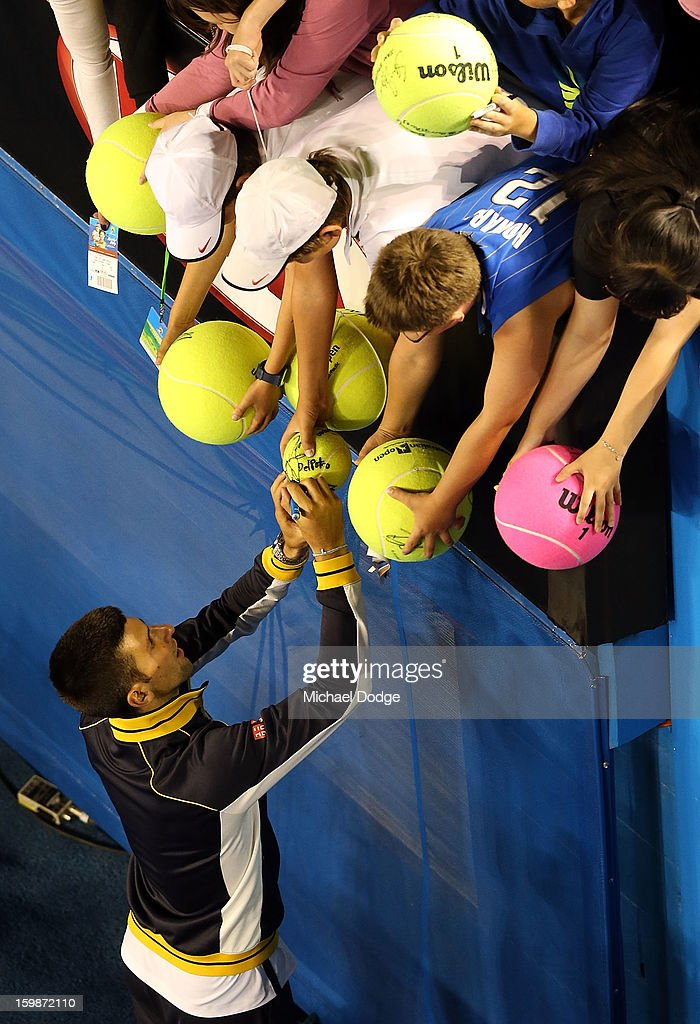 Novak Djockovic signs autographs for fans after his Quarterfinal match against Thomas Berdych of The Czech Republic during day nine of the 2013 Australian Open at Melbourne Park on January 22, 2013 in Melbourne, Australia.