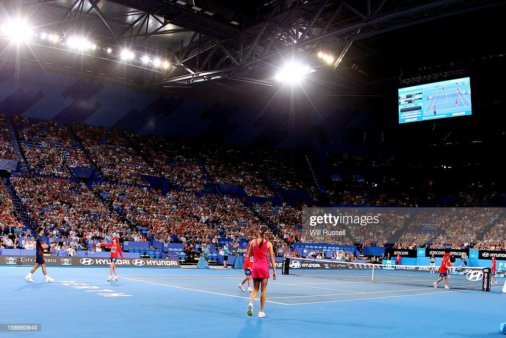 Novak Djokovic and Ana Ivanovic of Serbia look on as ballboys take their place in their mixed doubles match against Tatjana Malek and Thanasi Kokkinakis of Germany during day seven of the Hopman Cup at Perth Arena on January 4, 2013 in Perth, Australia.