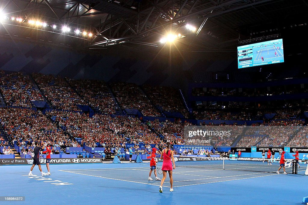 Novak Djokovic and Ana Ivanovic of Serbia looks on as ballboys take their place in their mixed doubles match against Tatjana Malek and Thanasi Kokkinakis of Germany during day seven of the Hopman Cup at Perth Arena on January 4, 2013 in Perth, Australia.