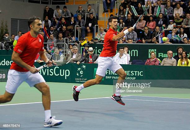 Novak Djokovic and Nenad Zimonjic of Serbia in action against Marin Draganja and Franko Skugor of Croatia during their men's double match on the day...