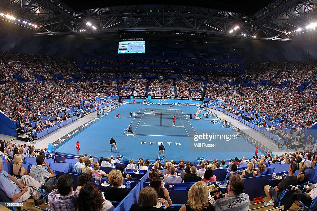 Novak Djokovic hits a forehand as Ana Ivanovic and of Serbia looks on in their mixed doubles match against Tatjana Malek and Thanasi Kokkinakis of Germany during day seven of the Hopman Cup at Perth Arena on January 4, 2013 in Perth, Australia.