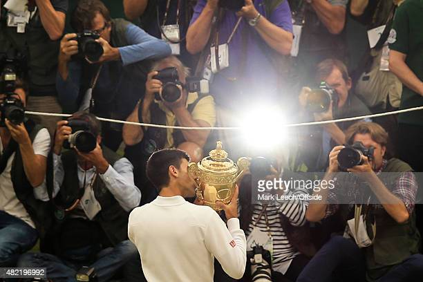 Novak Djokovic kisses the trophy in front of a bank of photographers after winning the gentlemen's final on day thirteen of the Wimbledon Lawn Tennis...