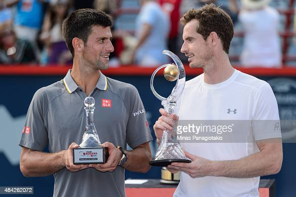 Novak Djokovic of Serbia and Andy Murray of Great Britain looks at one another as they hold their trophies during day seven of the Rogers Cup at...