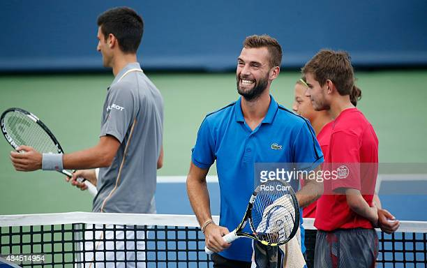 Novak Djokovic of Serbia and Benoit Paire of France talk during a rain delay in the start of their match during the Western Southern Open at the...