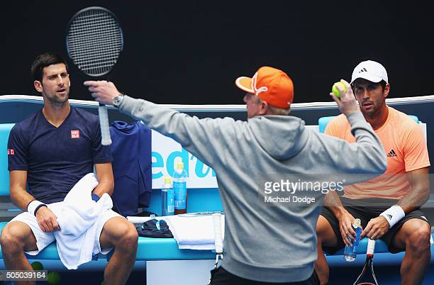Novak Djokovic of Serbia and Fernando Verdasco of Spain listen to Djockovic's coach Boris Becker during a practice session ahead of the 2016...