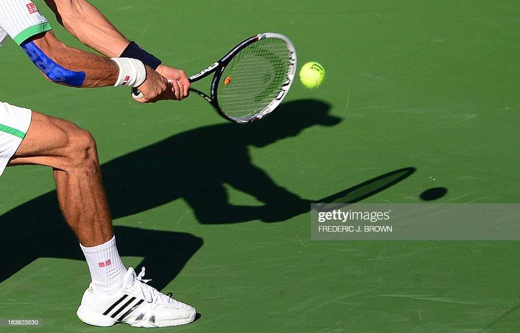 Novak Djokovic of Serbia casts a shadow on the court while playing a backhand return against Juan Martin Del Potro of Argentina on March 16, 2013 in Indian Wells, California, during their semifinal match at the BNP Paribas Open which Nadal won. AFP PHOTO/Frederic J. BROWN
