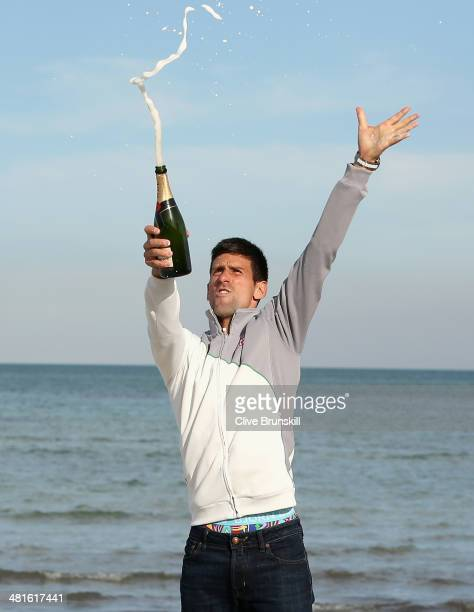 Novak Djokovic of Serbia celebrates by spraying champagne on Crandon Park beach after his straight sets victory against Rafael Nadal of Spain during...