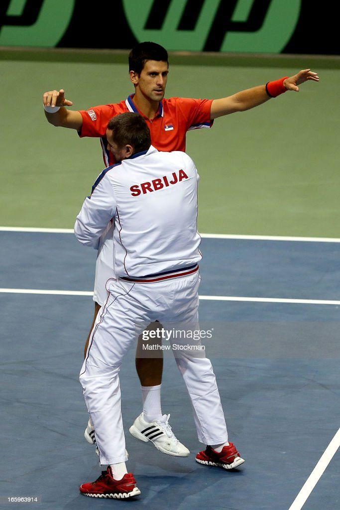 <a gi-track='captionPersonalityLinkClicked' href=/galleries/search?phrase=Novak+Djokovic&family=editorial&specificpeople=588315 ng-click='$event.stopPropagation()'>Novak Djokovic</a> of Serbia celebrates his win in the fourth rubber against Sam Querrey with team captain Team Captain Bogdan Obradovic of Serbia during the Davis Cup tie between the United States and Serbia at Taco Bell Arena on April 7, 2013 in Boise, Idaho.