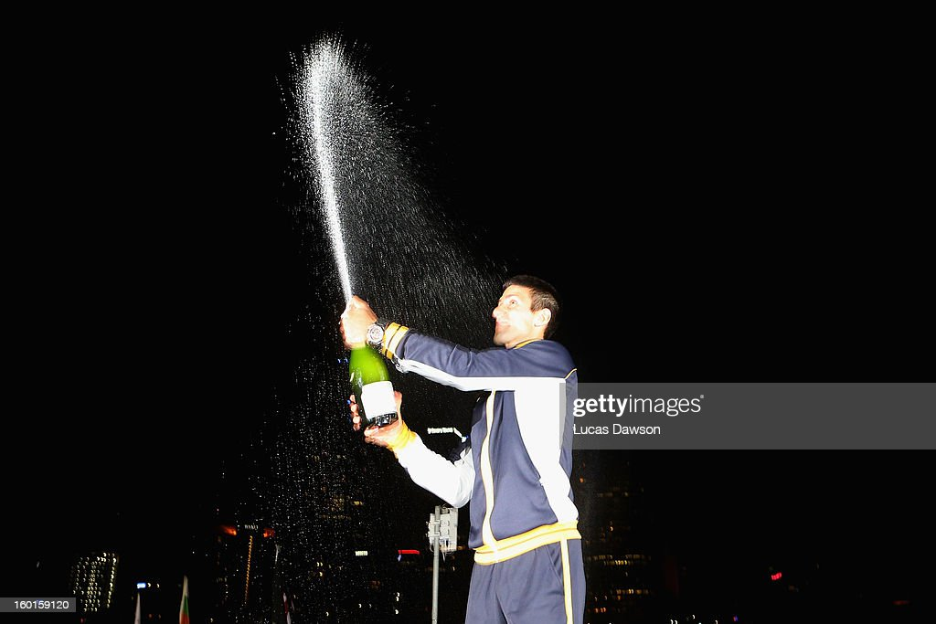 Novak Djokovic of Serbia celebrates with a bottle of champagne in the early hours of January 28, 2013 after winning his men's final match against Andy Murray of Great Britain during day fourteen of the 2013 Australian Open at Melbourne Park on January 27, 2013 in Melbourne, Australia.