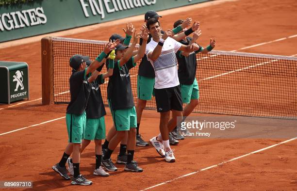 Novak Djokovic of Serbia celebrates with the ball boys after beating Marcel Granollers of Spain in their first round match on day two of the 2017...
