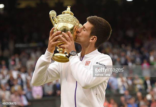 Novak Djokovic of Serbia celebrates with the trophy after winning the Final Of The Gentlemen's Singles against Roger Federer of Switzerland on day 13...