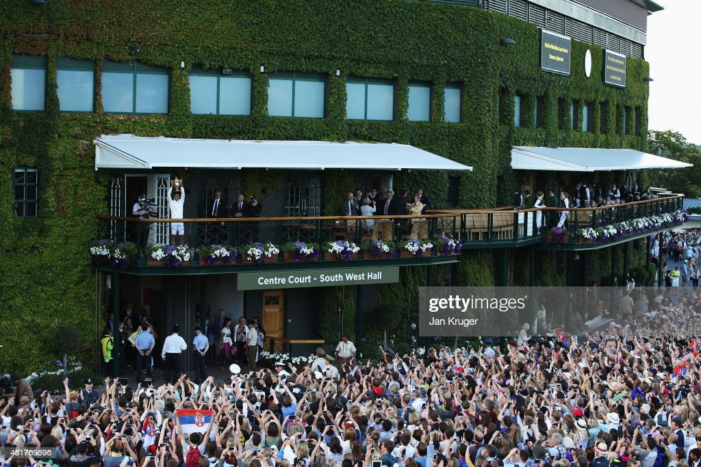 Novak Djokovic of Serbia celebrates with the trophy on the clubhouse balcony in front of a bank of fans after winning the Gentlemen's Singles Final against Roger Federer of Switzerland on day thirteen of the Wimbledon Lawn Tennis Championships at the All England Lawn Tennis and Croquet Club on July 6, 2014 in London, England.