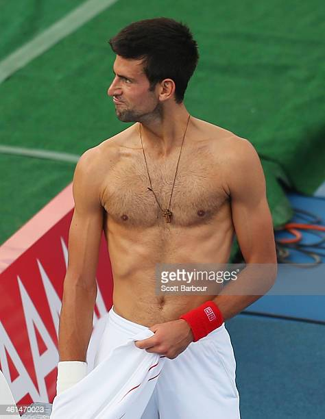 Novak Djokovic of Serbia changes his shirt during his match against Juan Monaco of Argentina during day two of the AAMI Classic at Kooyong on January...