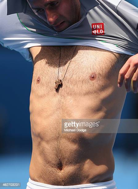 Novak Djokovic of Serbia changes his shirt in his second round match against Leonardo Mayer of Argentina during day three of the 2014 Australian Open...