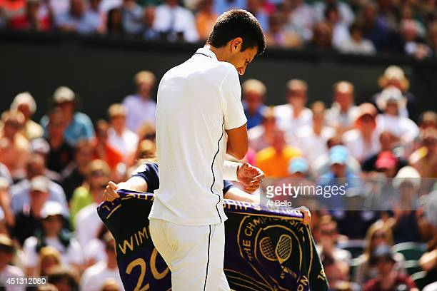 Novak Djokovic of Serbia clutches his injured shoulder as he walks back to his seat to receive treatment during his Gentlemen's Singles third round...