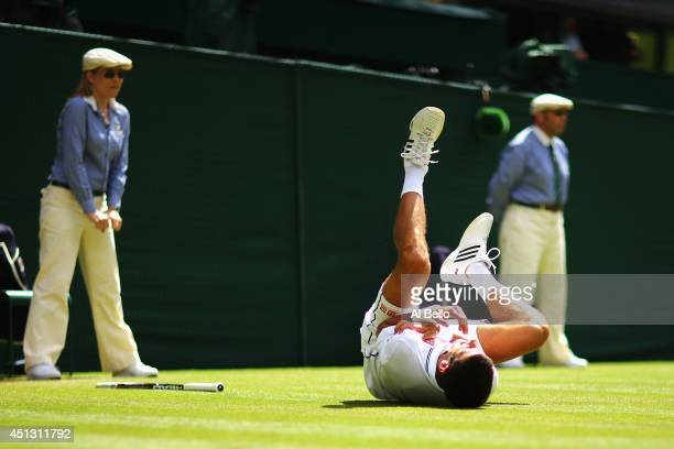 Novak Djokovic of Serbia clutches his shoulder which he injures after he falls over making a return during his Gentlemen's Singles third round match...