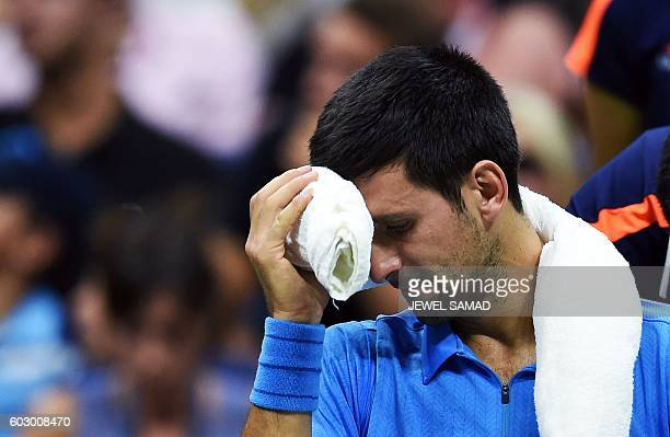 TOPSHOT Novak Djokovic of Serbia cools off during a break while playing against Stan Wawrinka of Switzerland in their 2016 US Open Men's Singles...